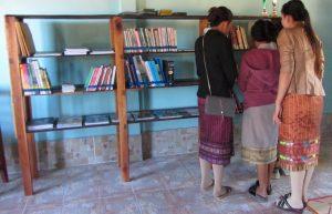 3 femmes regardent une étagère de la bibliothèque de Ban Houei